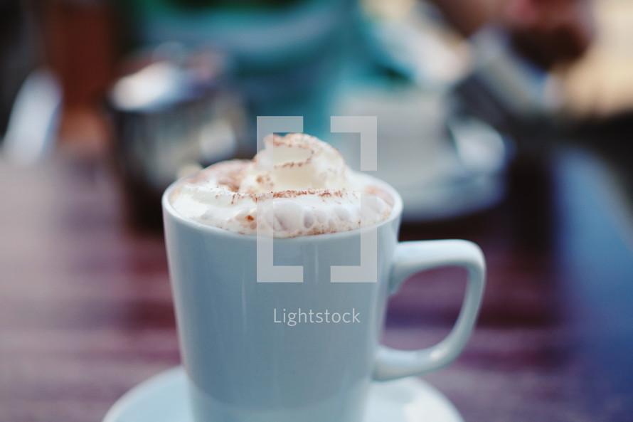 whip cream in a teal coffee mug