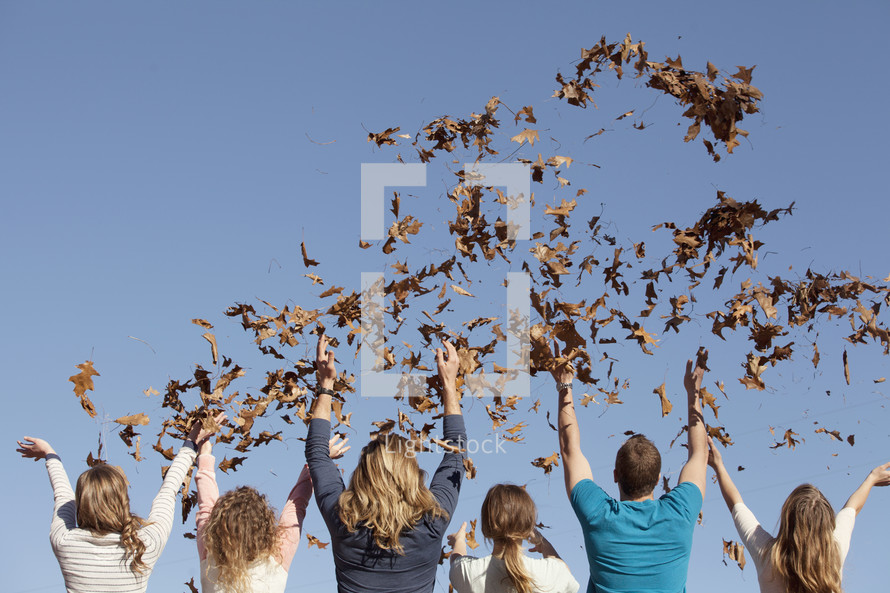 Group of friends throwing leaves in the air.