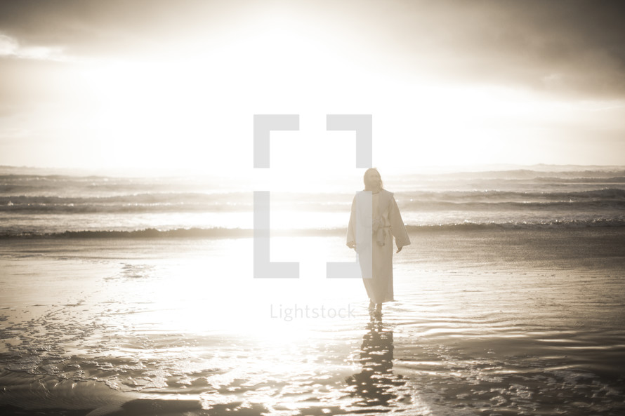 Jesus standing on a beach at sunrise