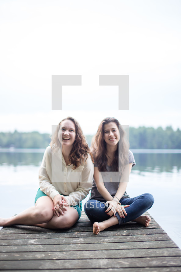 Friends sitting on a wooden pier on a lake.