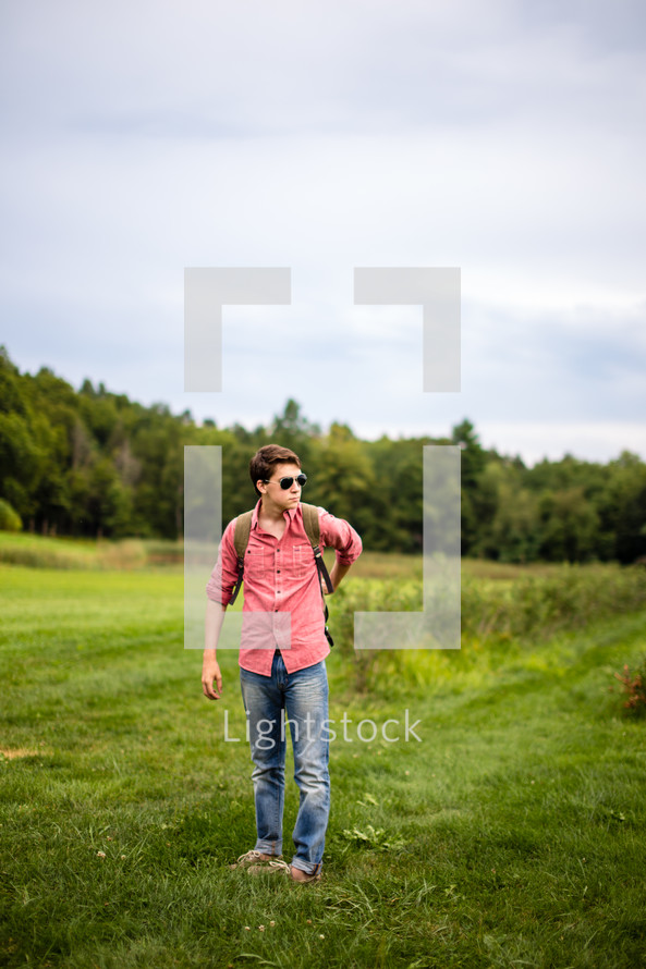 man in a field with a backpack