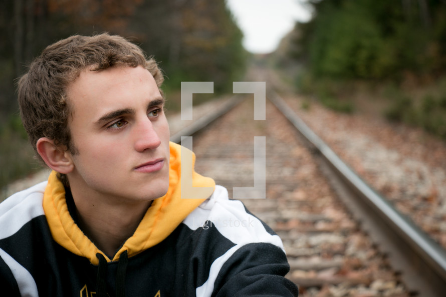man sitting on railroad tracks