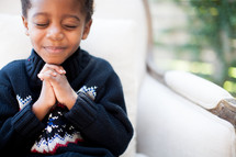 a boy child with praying hands