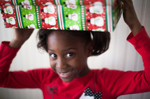 a girl child holding a Christmas gift over her head