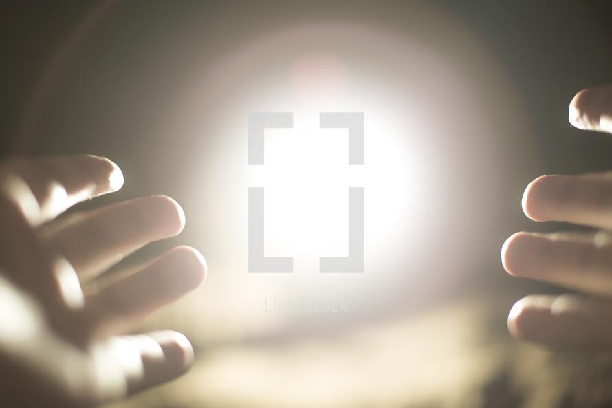a hand reaching towards glowing light