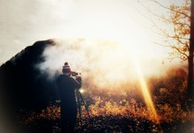 a man with a camera taking pictures through the fog at sunrise