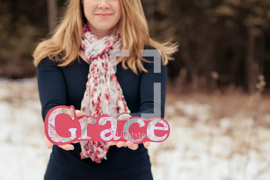 Woman standing outside in the snow holding a grace sign.