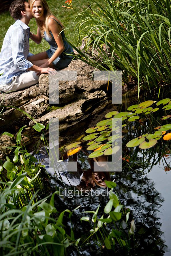 A husband kissing his wife beside a pond