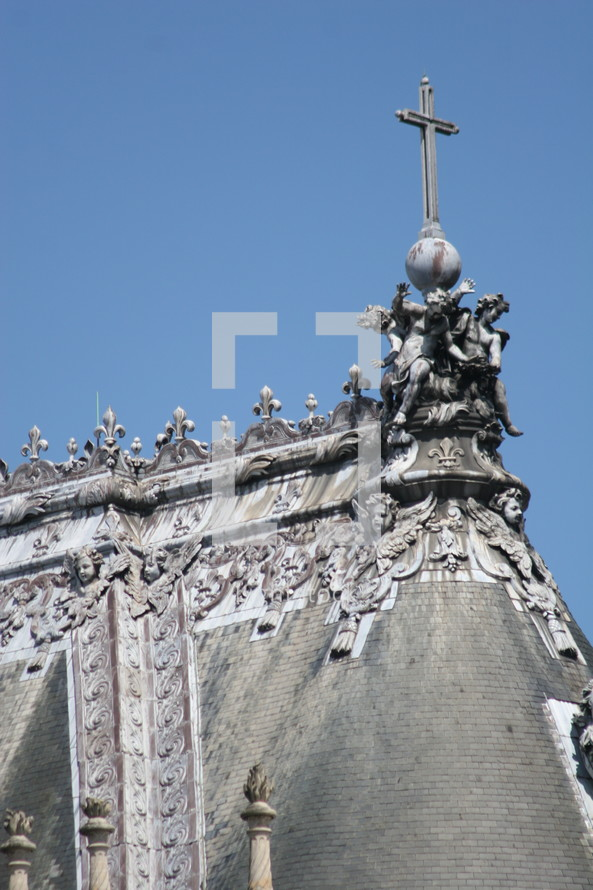 cross on an ornate rooftop