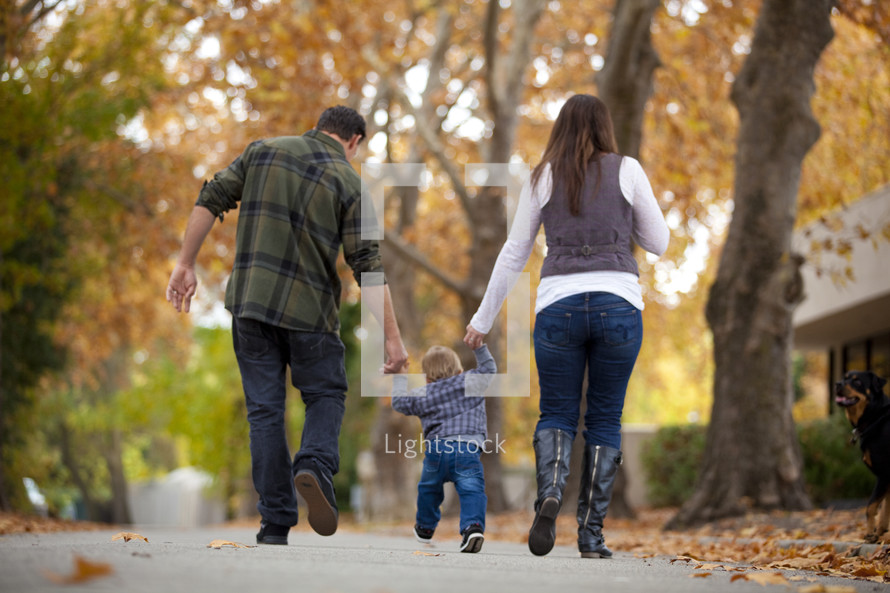 Mother and father walking outdoors with toddler