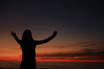 Woman with arms raised at sunset