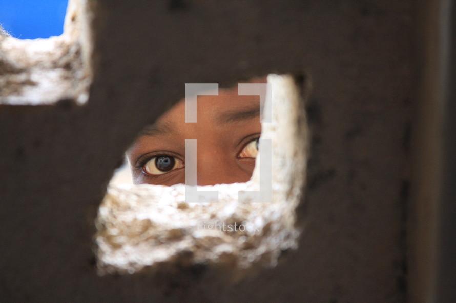 A child peeking through a hole in a wall.