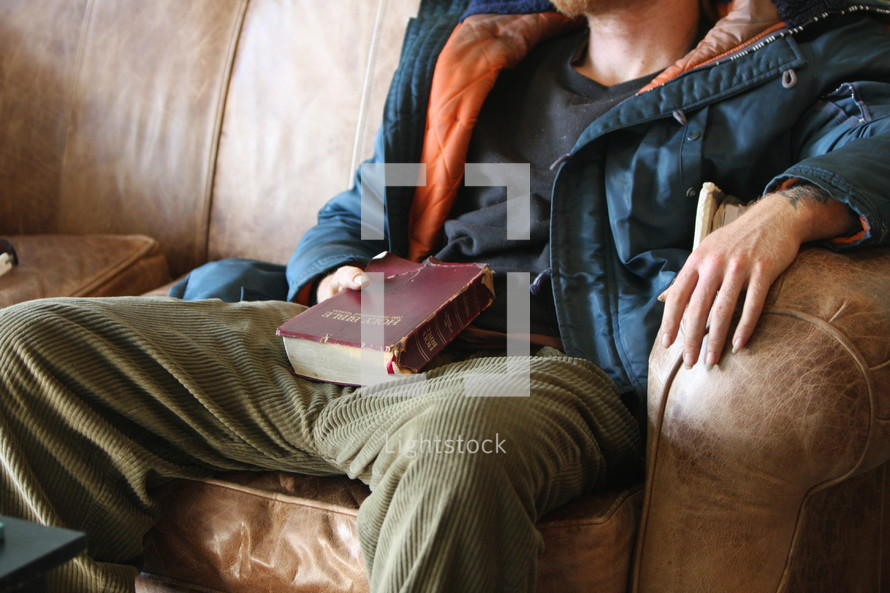 Homeless man holding worn Bible