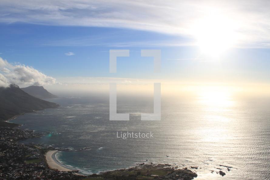 sunburst over the ocean near a coastline