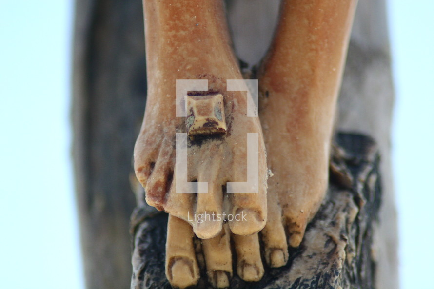feet of a statue of Jesus with nail