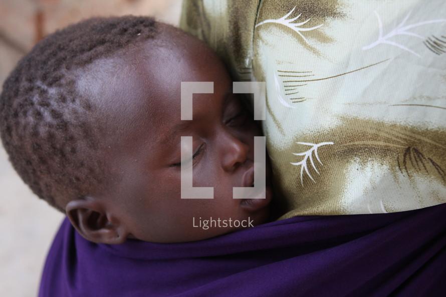 sleeping infant against mothers back