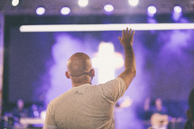 man standing with hand raised at a worship service