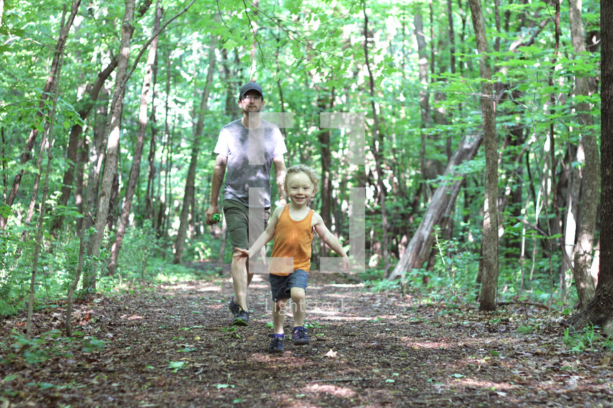 father and son running through a forest