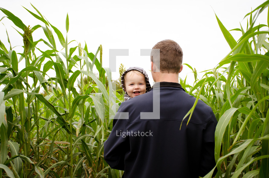 a father carrying his son through a tall corn field