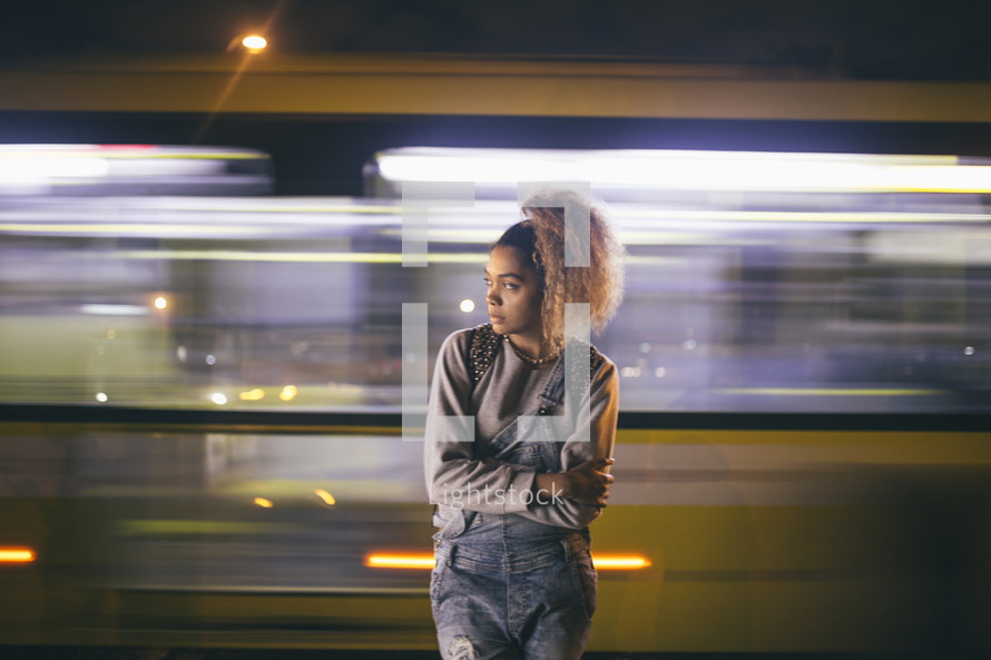 woman standing in front of a passing bus