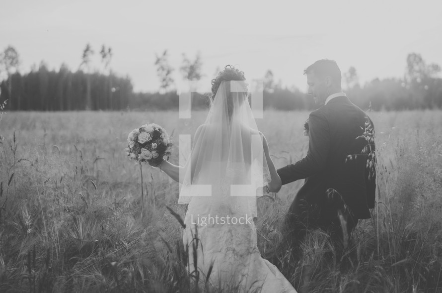 a bride and groom walking through a field of tall grasses