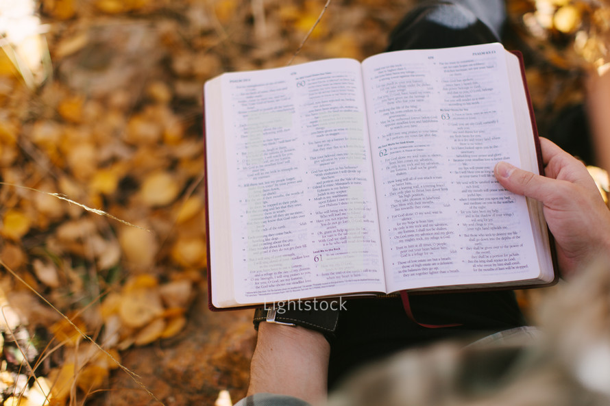reading a bible standing in fall leaves