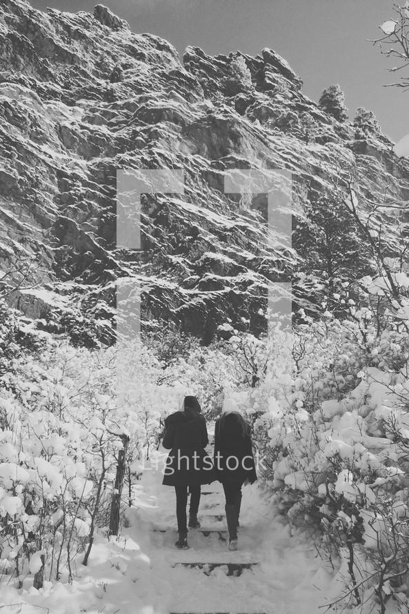 women walking up steps in the snow