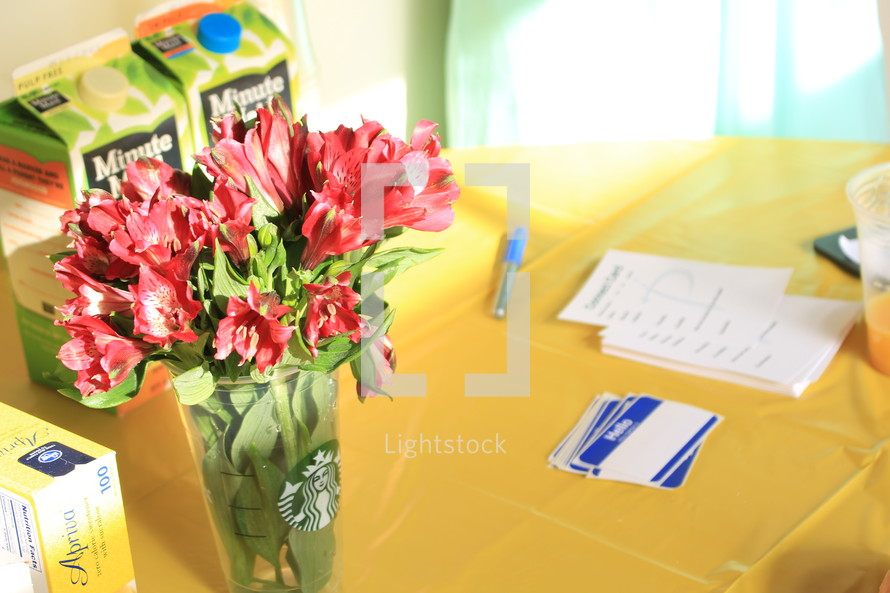orange juice cartons, flowers in a Starbucks cup, name tags, pen and lists at a registration table