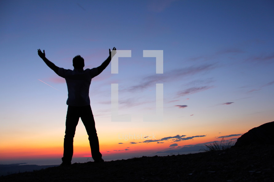 silhouette of a man with raised hands against the rising sun