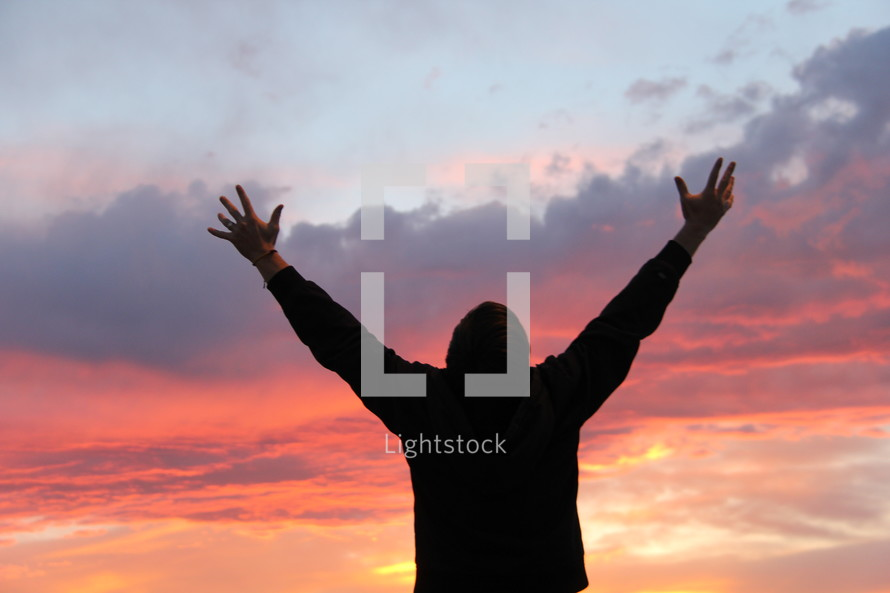 man with his arms raised praising God
