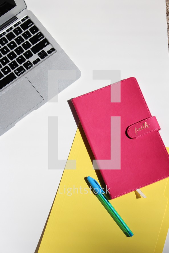 laptop computer, journal, file, and pen on a desk