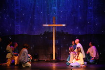 performers on stage kneeling in front of a cross and a scene of Bethlehem
