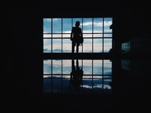 silhouette of a man standing in front of a window
