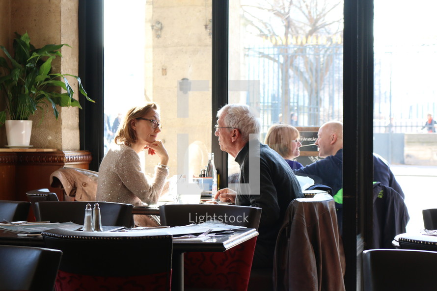 mature couples sitting in a restaurant in conversation