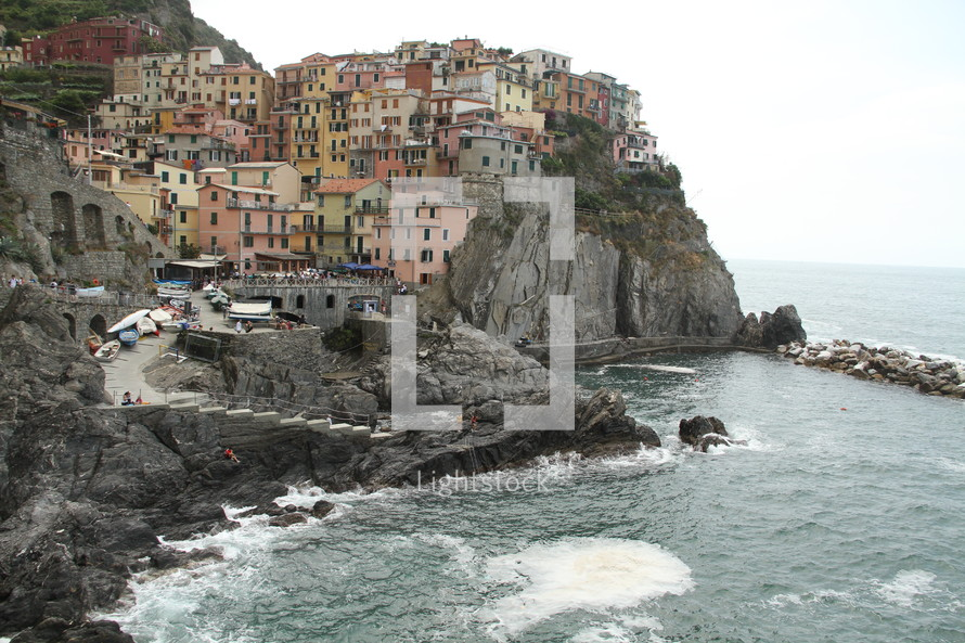 Village of homes on cliffside overlooking ocean.