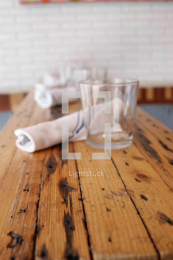 napkins and glasses on a wooden table