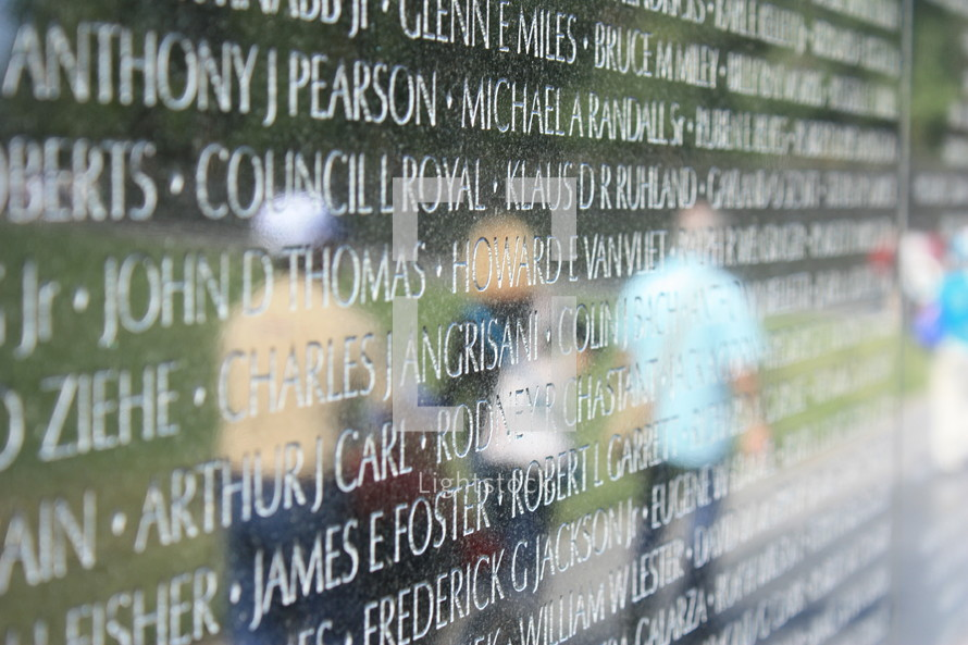 Reflection of people in the Vietnam Memorial wall where names are carved.