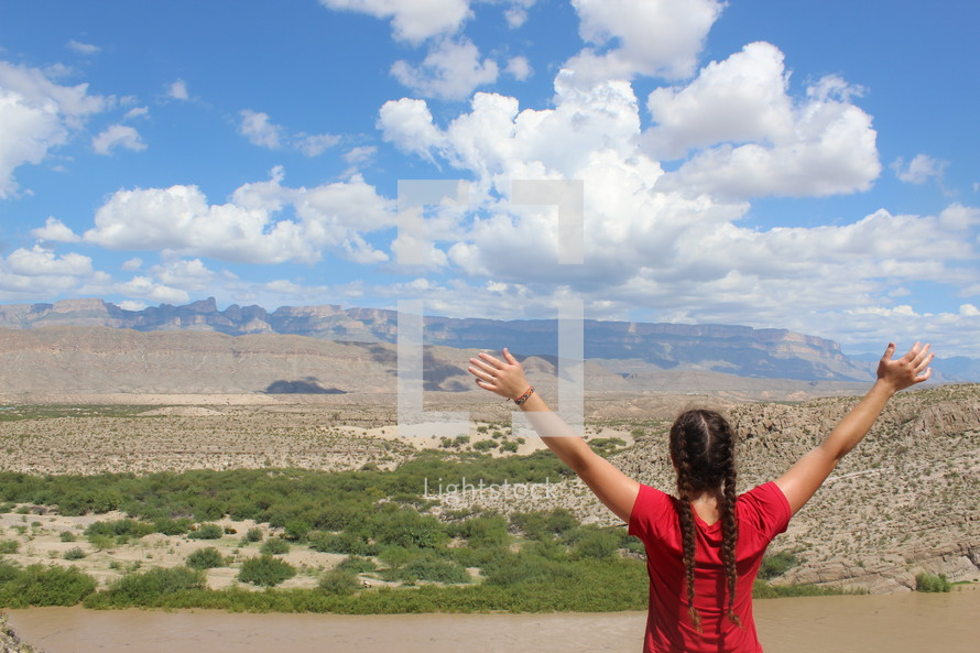 a woman standing outdoors with arms raised