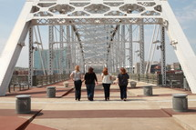 group of women walking on a bridge