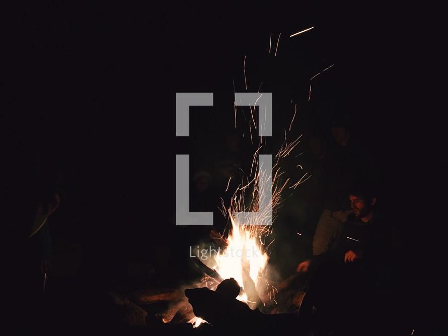 men sitting around a fire pit
