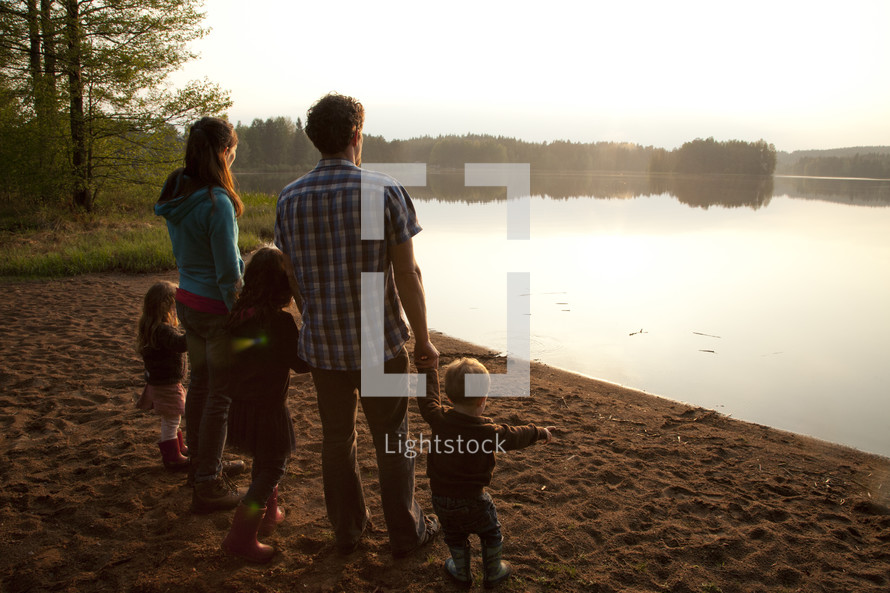 a young family standing on a lake shore holding hands in fall