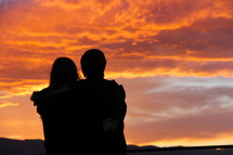 silhouette of a couple under an orange sky at sunset