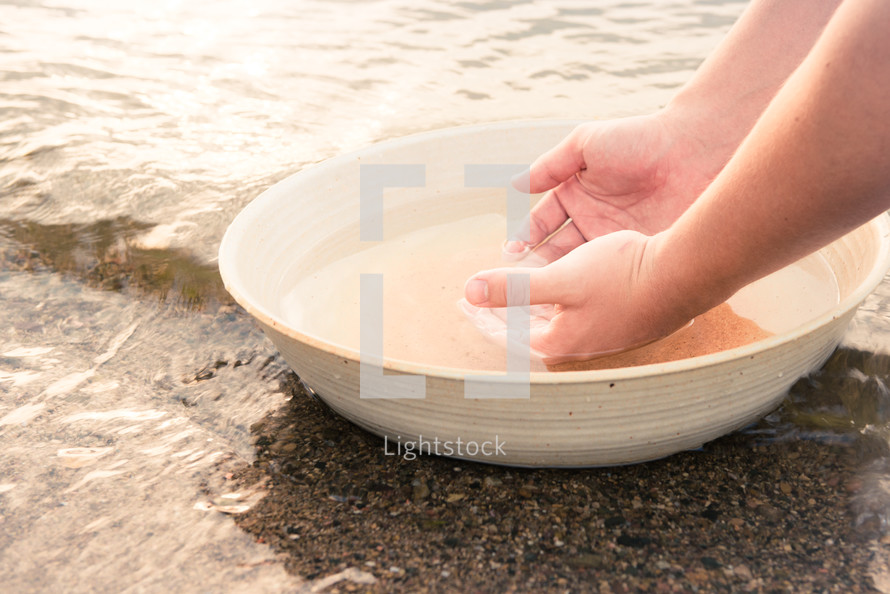 a woman washing her hands in a bowl of water