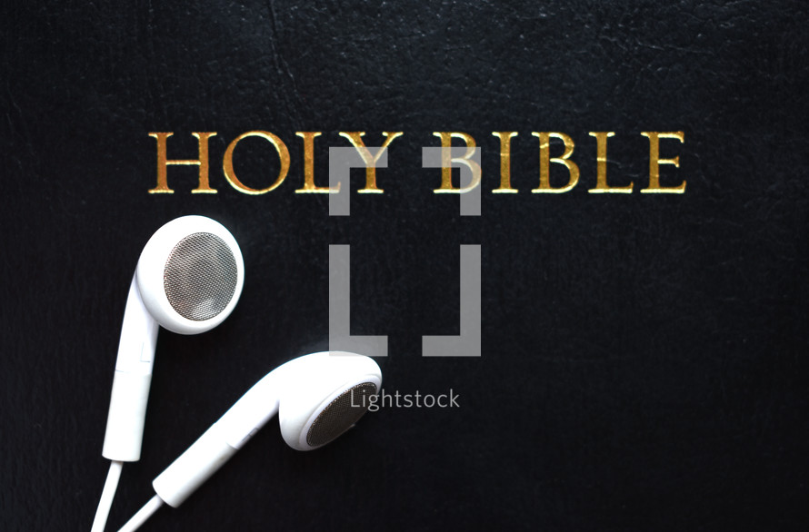 Holy Bible and earbuds