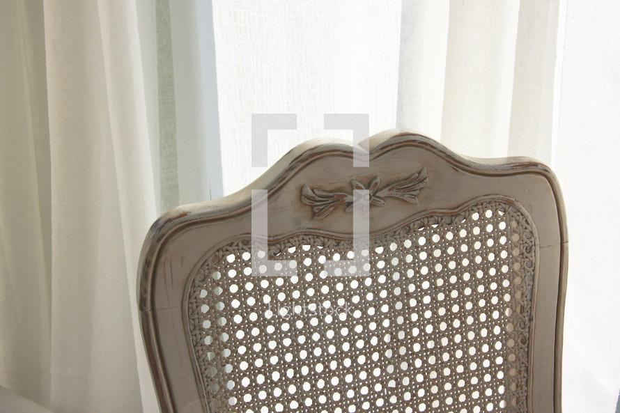 wicker back chair in a window