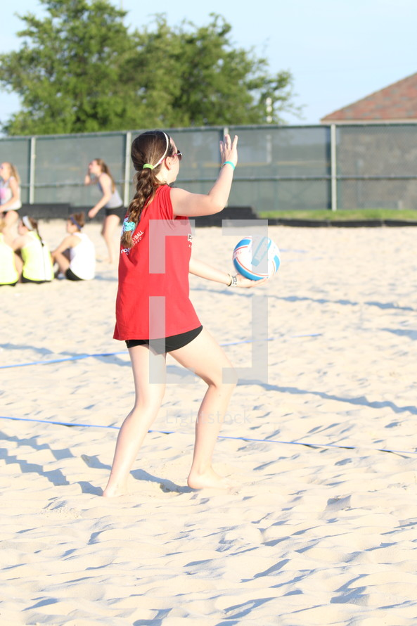 a teen girl playing volleyball in the sand