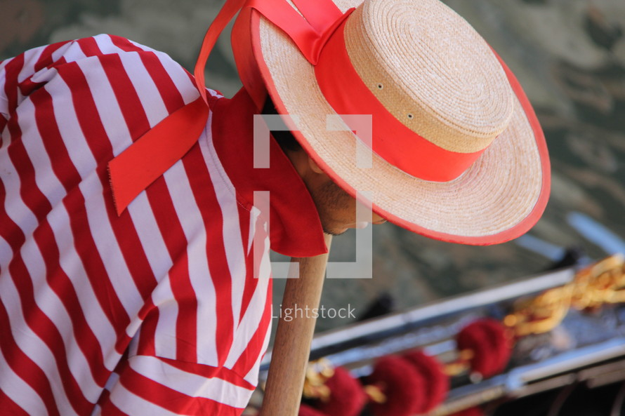 Gondolier in traditional striped top, straw hat with flowing ribbon