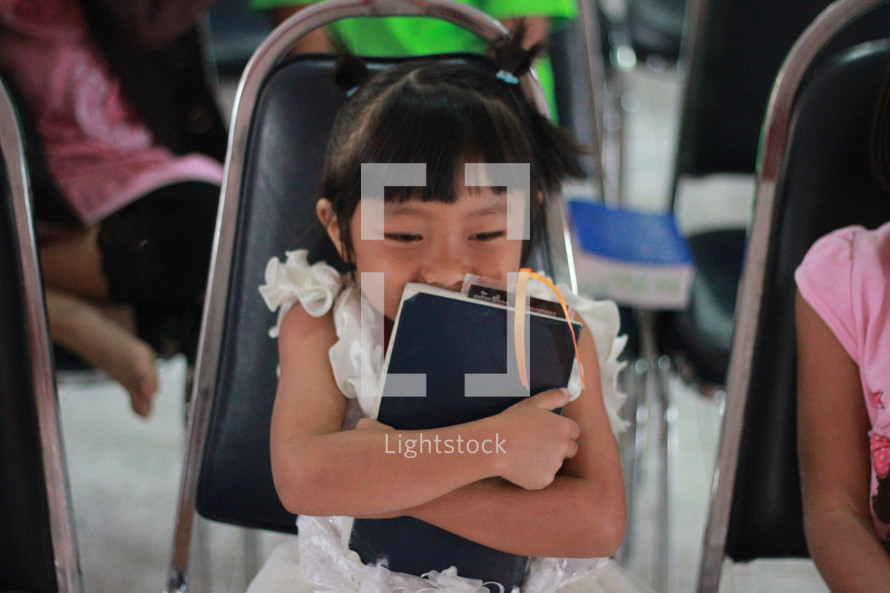Little girl in Thailand with her beloved BIBLE