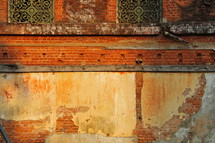brick wall on the side of an old house with missing plaster