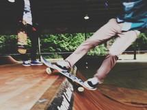 Teen boys skateboarding at a skate park.